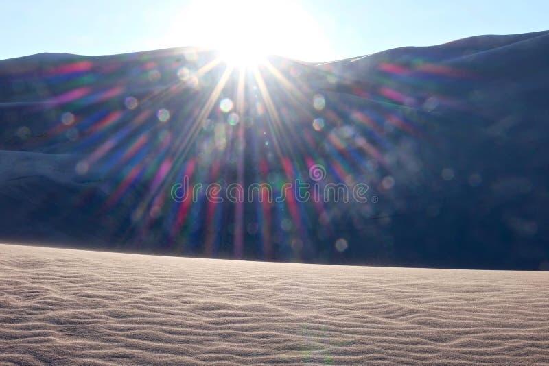 Лучи захода солнца над песчанными дюнами и горами стоковые изображения