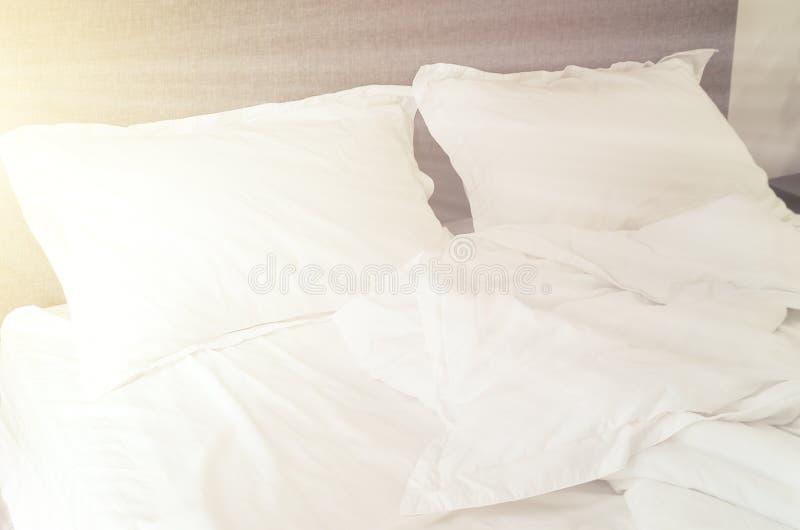 Лучи солнца в спальне, пустой кровати, белой подушке и поднимающем вверх одеяла близком стоковые изображения rf