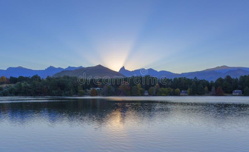 Лучи Солнця освещают вверх небо от за горного пика стоковое фото rf