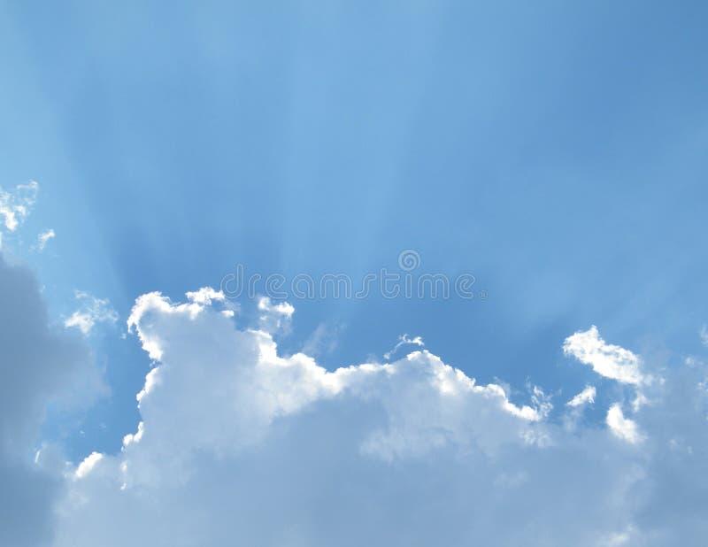 Лучи Солнця течь за тучными белыми облаками в небе стоковая фотография rf