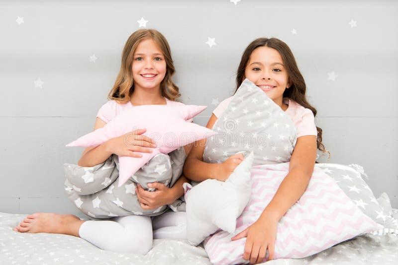 Лучшие други или братья девушек счастливые в милых стильных пижамах с партией sleepover подушек Сестры играют спальню подушек стоковое фото