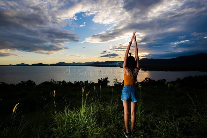 Луч облака захода солнца к молодому взрослому азиатскому woma стоковое фото
