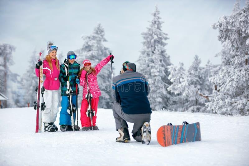 Лыжа, солнце снега и потеха - семья на празднике лыжи фотографируя стоковое изображение