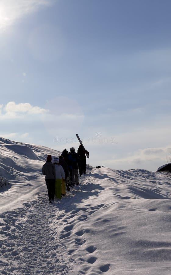 Лыжники и snowboarders идут вверх на снежную дорогу на утре зимы стоковое фото