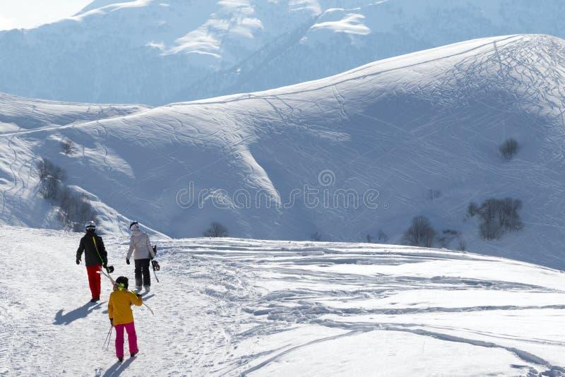 Лыжники и snowboarders на снежной дороге на утре зимы солнца стоковые изображения
