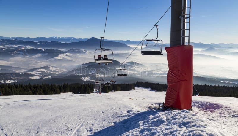 Лыжники на подвесном подъемнике Следы лыжи стоковые изображения