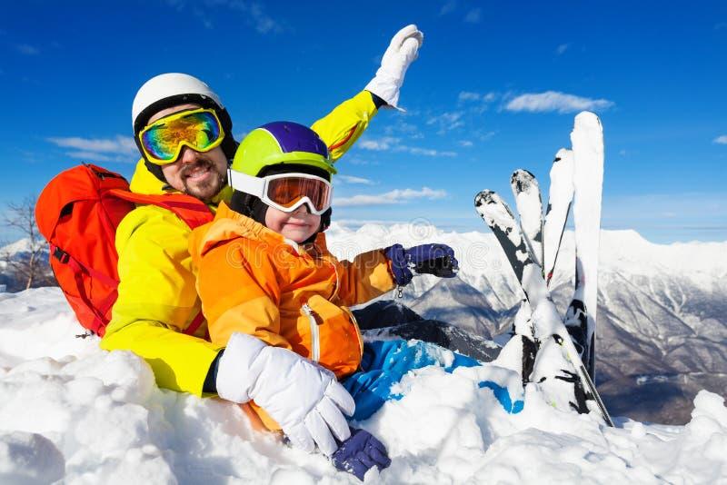 Лыжники папы и сына сидят в снеге на верхней части горы стоковые изображения rf
