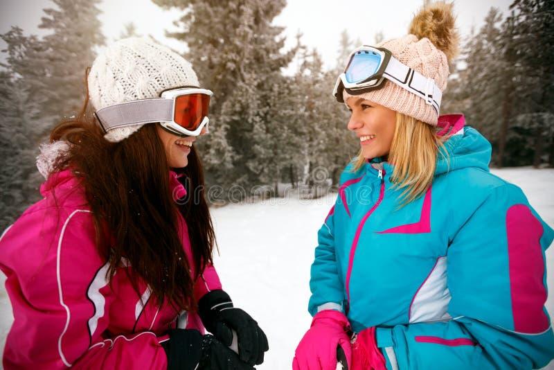Лыжники подруг стоя на наклоне лыжи стоковое фото rf