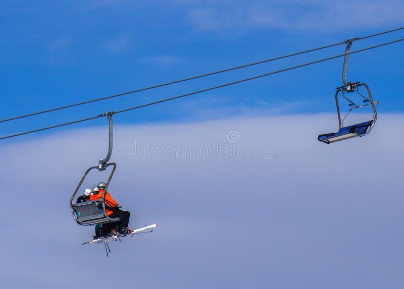 Лыжники сидя в подъеме лыжи стоковые фотографии rf