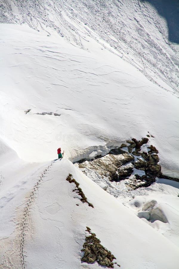 Лыжник взбираясь снежная гора стоковое изображение rf