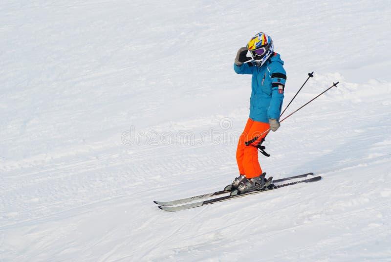 Лыжник едет на снежных горных склонах стоковое изображение