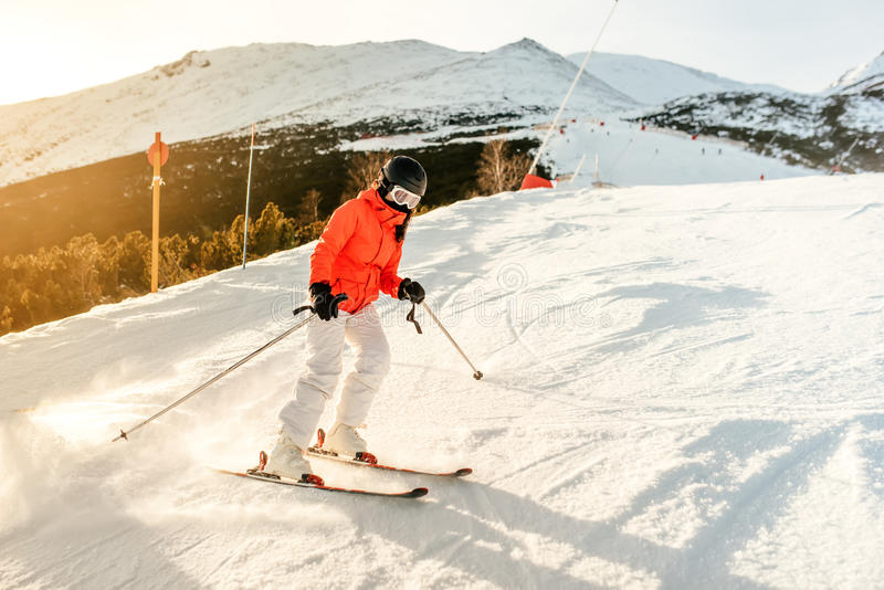 Лыжник женщины на наклоне в горы Катание на лыжах девушки на солнечный день стоковая фотография