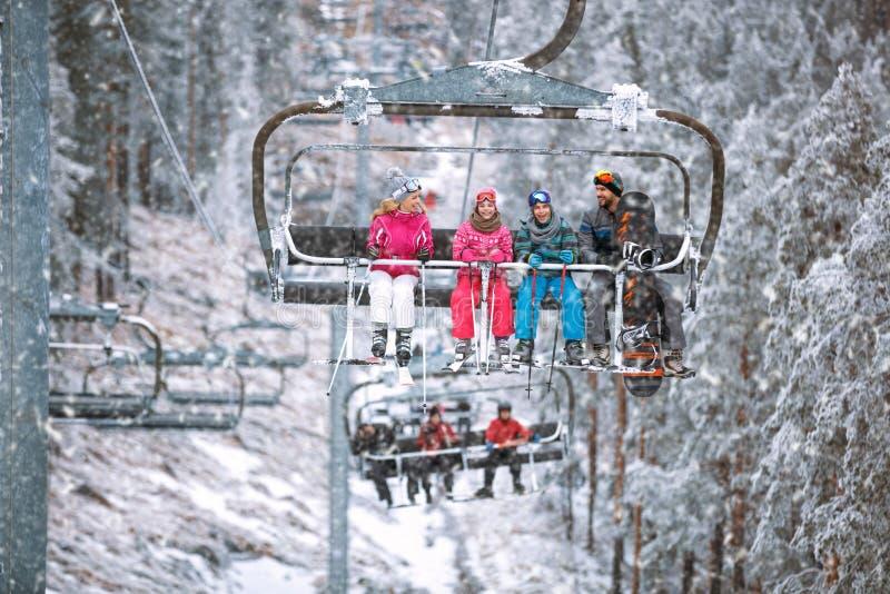 Лыжник и snowboarder семьи поднимаясь на подвесной подъемник на лыже res стоковые фотографии rf