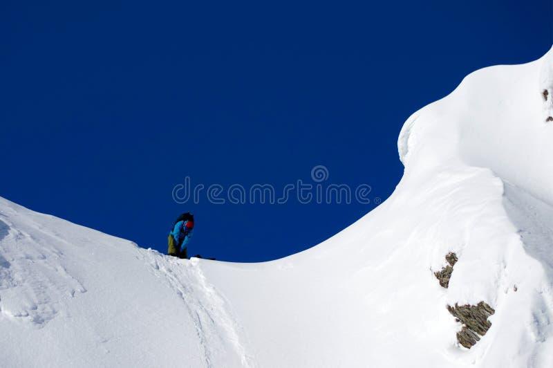 Лыжник на верхней части горы в солнечном зимнем дне стоковая фотография