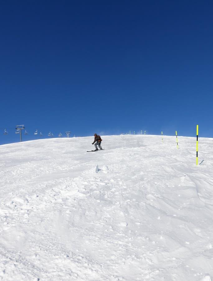 Лыжник покатый на снежном горнолыжном склоне в солнечном зимнем дне стоковая фотография