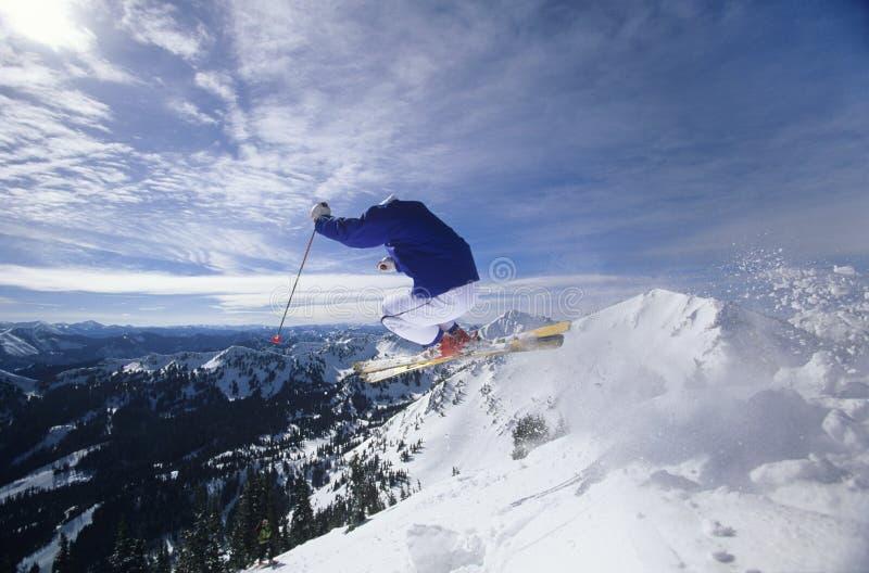 Лыжник скача на верхнюю часть горы ударяя наклоны стоковая фотография rf