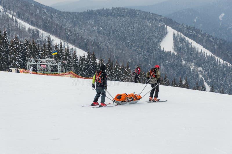 Лыжник спасения команды патруля лыжи раненый с специальными непредвиденными розвальнями в зоне прикарпатских гор, Украиной стоковые изображения