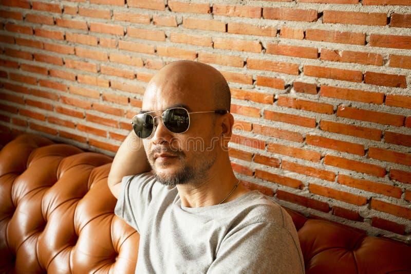 лысый человек портрета бороды 30-40s сидя на софе с краснокоричневой предпосылкой внутренней стены кирпича стоковые фото