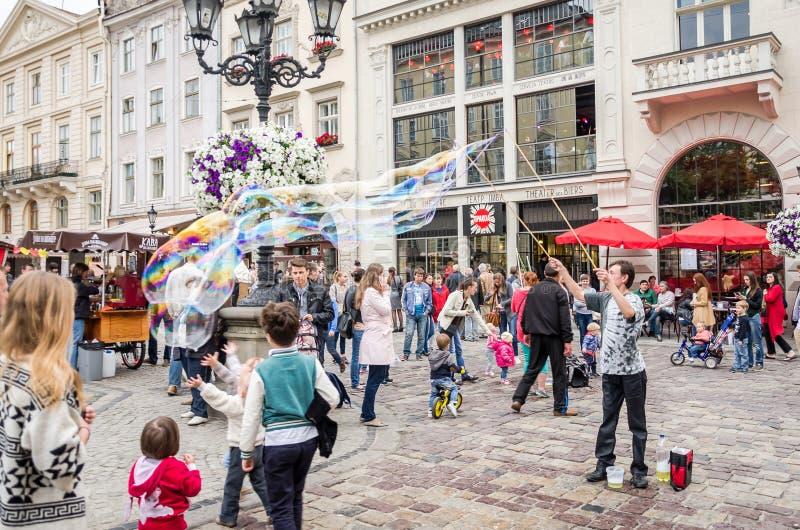Львов Украина июнь 2015: Гай развлекает детей в центре  Львова на рыночной площади для детей начиная огромные пузыри мыла стоковая фотография rf