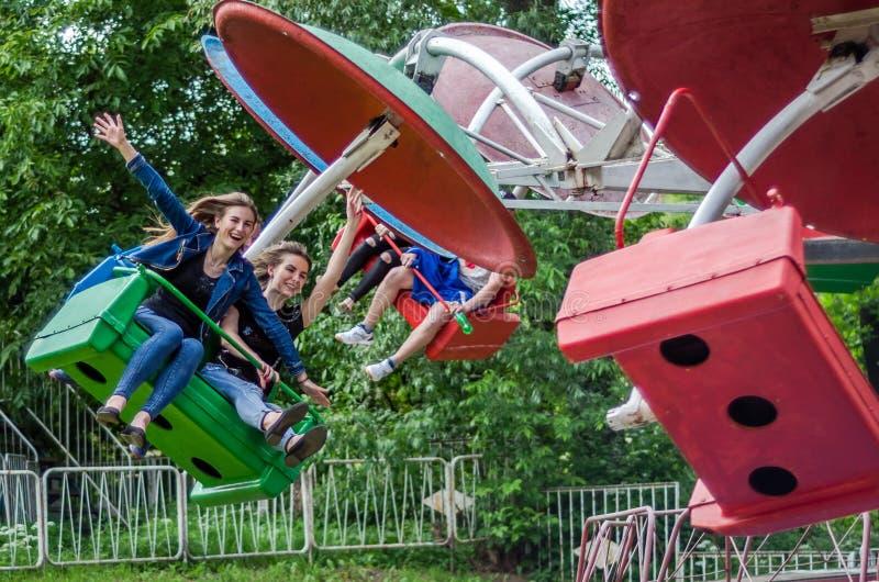 ЛЬВОВ, УКРАИНА - ИЮНЬ 2016: 2 красивых подростка маленьких девочек едет на carousel в парке атракционов, с счастливыми радостными стоковая фотография rf
