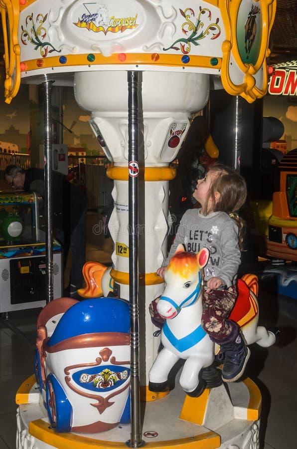ЛЬВОВ, УКРАИНА - ЯНВАРЬ 2018: Маленькая очаровательная девушка ребенок идет для езды в парке атракционов на carousel и играх виде стоковые фото