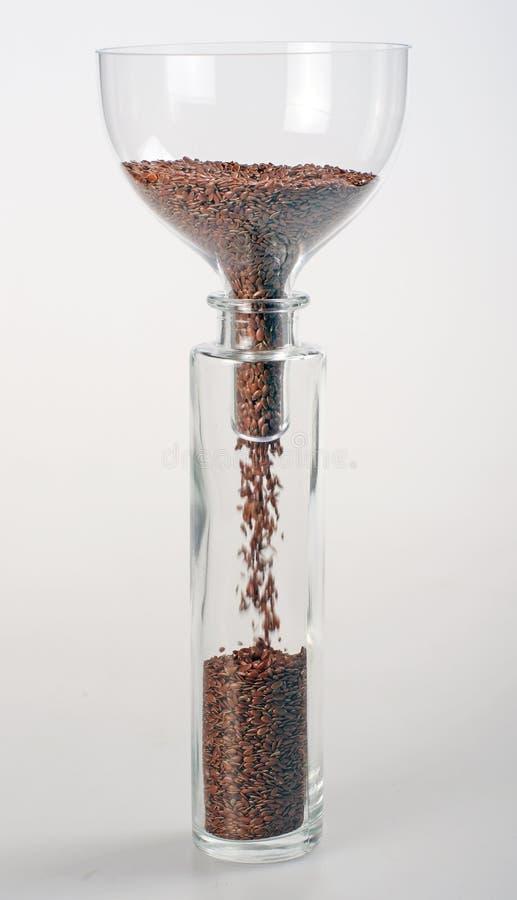 Льняное семя падая вниз в бутылку стоковые изображения