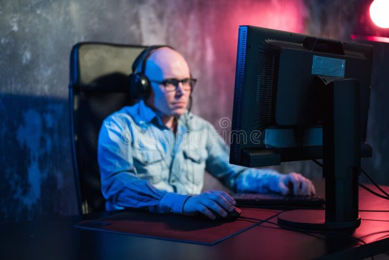 Любимое хобби Выборочный профиль сконцентрированного молодого gamer в наушниках сидит в клубе компьютера Игра виртуальная стоковое изображение