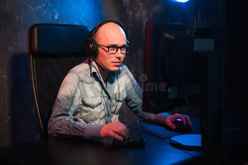Любимое хобби Выборочный профиль сконцентрированного молодого gamer в наушниках сидит в клубе компьютера Игра виртуальная стоковая фотография rf