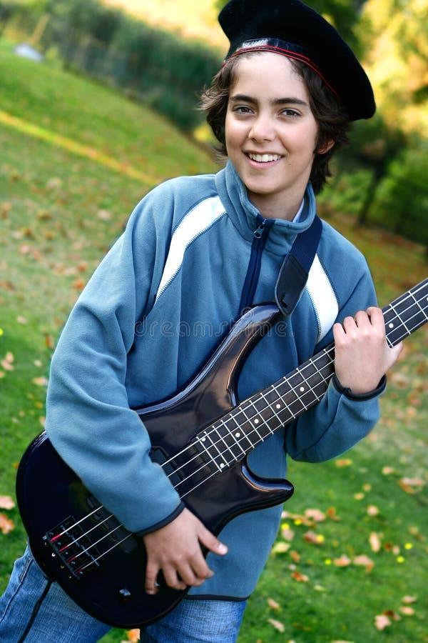 любимые детеныши гитары мальчика стоковое фото rf