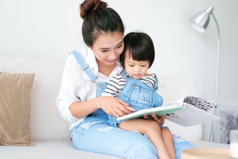 любить семьи счастливый Довольно молодая азиатская мать читая книгу к стоковая фотография
