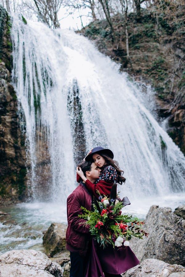 Любить, стильная, молодая пара в любов на предпосылке водопада стоковая фотография
