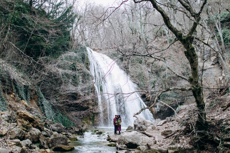 Любить, стильная, молодая пара в любов на предпосылке водопада стоковые фото
