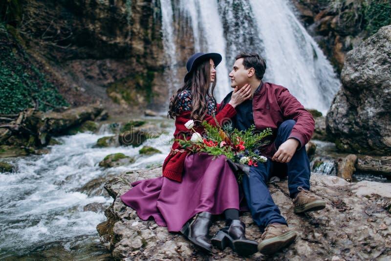 Любить, стильная, молодая пара в любов на предпосылке водопада стоковое изображение