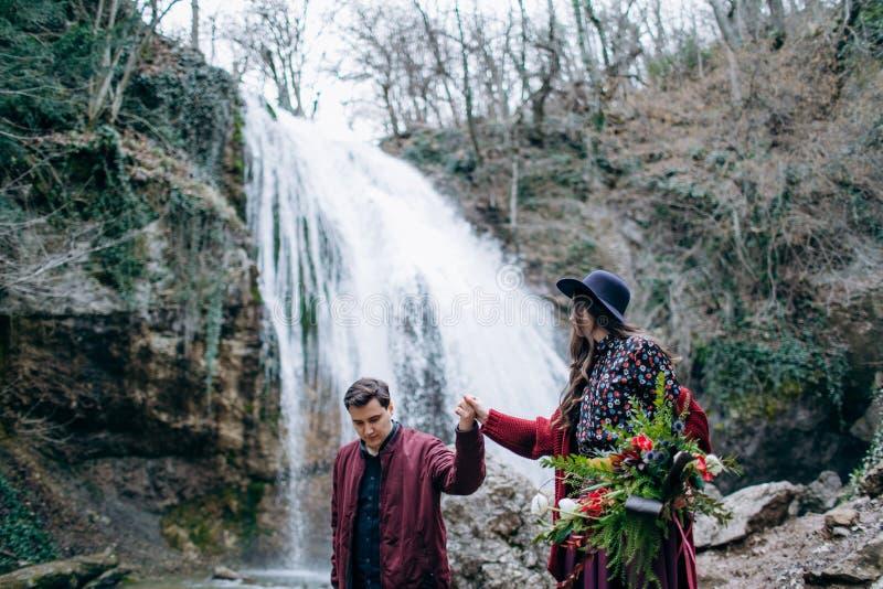 Любить, стильная, молодая пара в любов на предпосылке водопада стоковые изображения