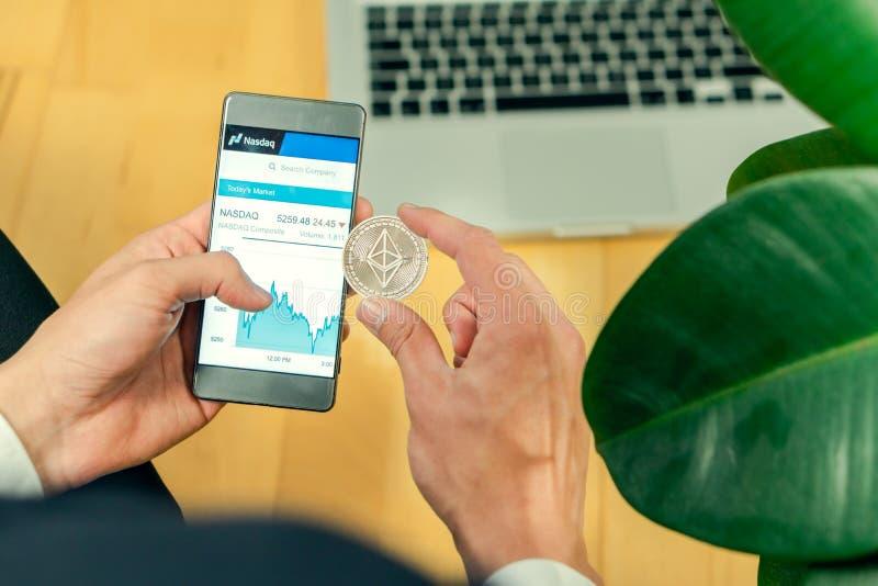Любляна, Словения 29 4 2019: Бизнесмен держа мобильный смартфон с раскрытым вебсайтом NASDAQ и монетку Ethereum на a стоковое изображение