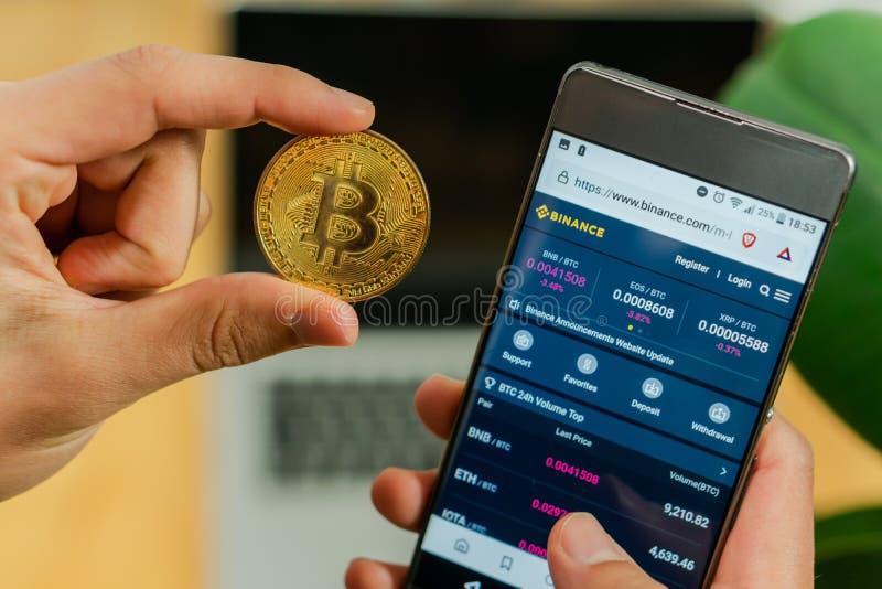 Любляна, Словения 29 4 2019: Бизнесмен держа мобильный смартфон с раскрытым вебсайтом Binance и монетку Bitcoin на a стоковая фотография