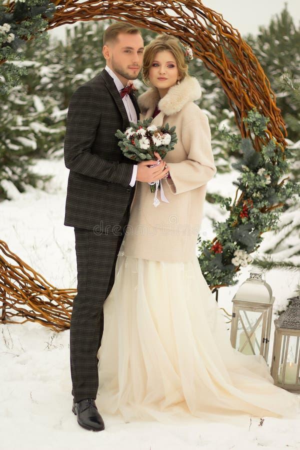 2 любовника, человек и женщина, свадьба в зиме Влюбленность жениха и невеста против фона оформления и деревьев, снег Держать a стоковое фото rf