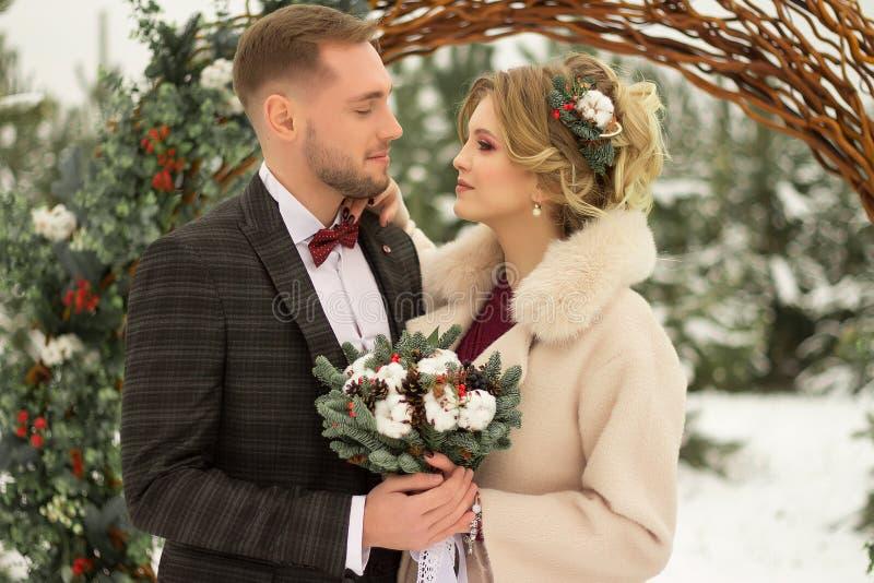 2 любовника, человек и женщина, свадьба в зиме Влюбленность жениха и невеста против фона оформления и деревьев, снег Держать a стоковые фотографии rf