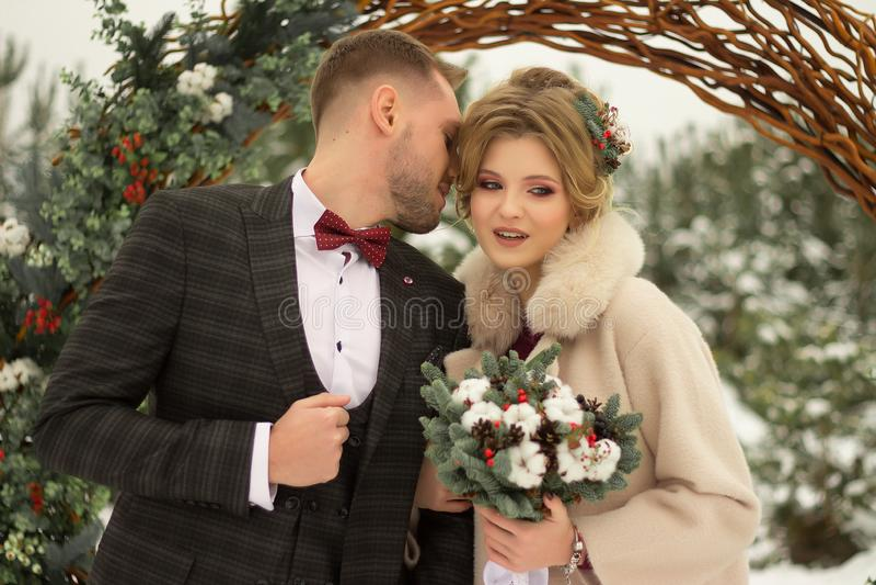 2 любовника, человек и женщина, свадьба в зиме Влюбленность жениха и невеста против фона оформления и деревьев, снег Держать a стоковая фотография rf