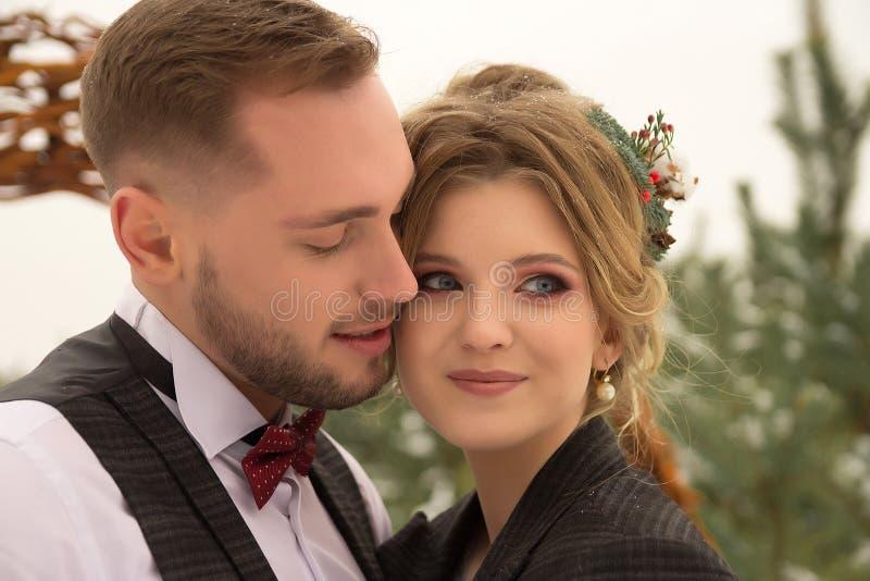 2 любовника, человек и женщина, свадьба в зиме Влюбленность жениха и невеста против фона оформления и деревьев, снег Держать a стоковые изображения rf