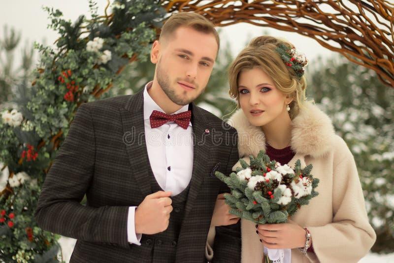 2 любовника, человек и женщина, свадьба в зиме Влюбленность жениха и невеста против фона оформления и деревьев, снег Держать a стоковое изображение