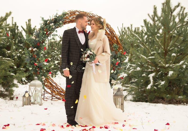 2 любовника, человек и женщина, свадьба в зиме Влюбленность жениха и невеста против фона оформления и деревьев, снег Держать a стоковая фотография