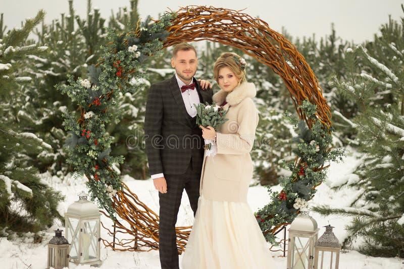 2 любовника, человек и женщина, свадьба в зиме Влюбленность жениха и невеста против фона оформления и деревьев, снег Держать a стоковое изображение rf