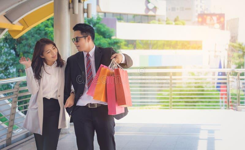 Любовники, женщины и люди нося много бумажных сумок, счастливо ходя по магазинам стоковые изображения rf