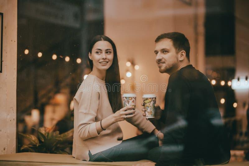 Любовники парень и девушка одетые в свитерах и джинсах сидят близко к одину другого на windowsill в кафе и стоковые фото