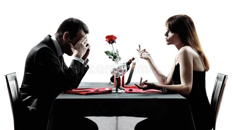 Любовники пар датируя силуэты спора обедающего стоковые фотографии rf