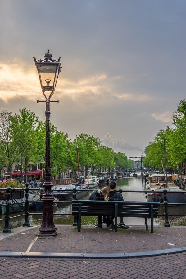 Любовники сидят совместно на сумерк обозревая канал в Амстердаме стоковые фотографии rf