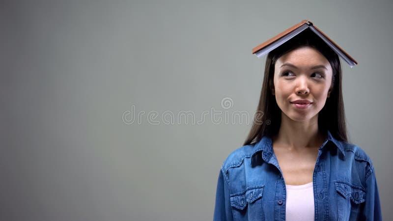 Любовник литературы с книгой на голове смотря в сторону, список порекомендованных романов стоковые изображения
