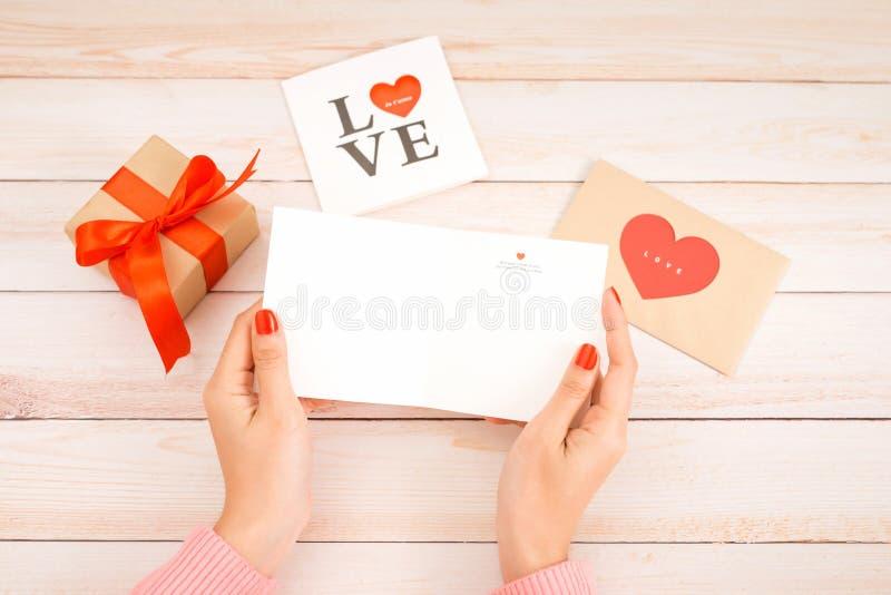 Любовное письмо дня Валентайн на деревянной предпосылке Красные печенья, конфета и кофе формы сердца бархата Женские руки с красн стоковая фотография