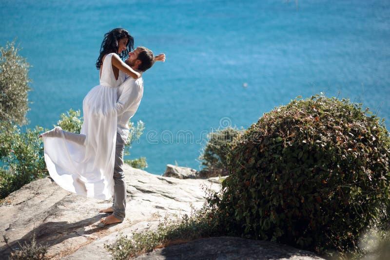 Любовь в воздухе, beautyful паре embrancing, имеет медовый месяц в Греции, летом, изолированной на предпосылке моря стоковая фотография rf